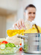 Woman in yellow pours oil  into saucepan