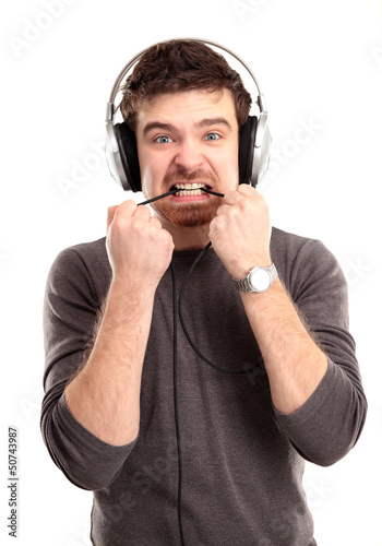 young man listening to music and biting a wire
