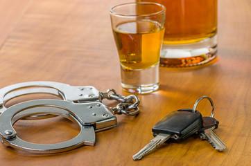Schnapsglas mit Autoschlüssel und Handschellen