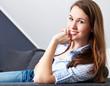 Attraktive junge Frau sitzt entspannt auf der Couch