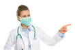 Medical doctor woman in mask pointing on copy space