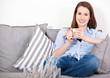 Attraktive junge Frau genießt einen Kaffee auf der Couch
