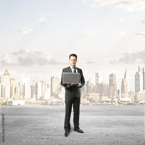 businessman with laptop and city on background