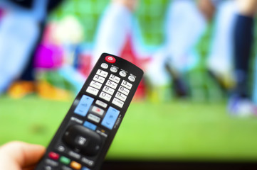 Close-up of modern remote control, watching a soccer game on TV