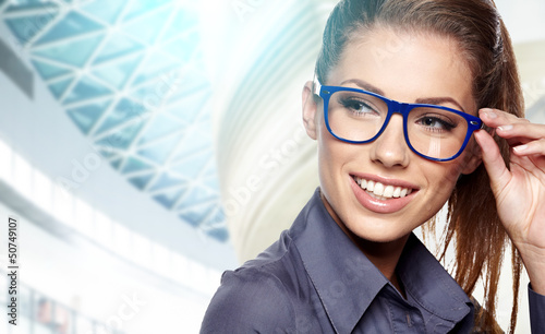 business woman holding glasses and looking at camera.