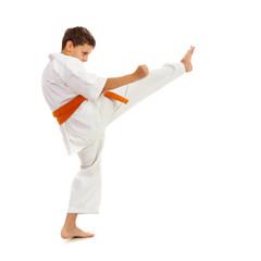 Young boy in kimono making kick