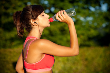 Beautiful fit latina drinking water after training