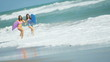 Girls Splashing Ocean Carrying Body Board