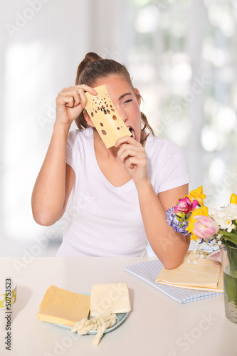 Young woman peeping through a cheese with holes