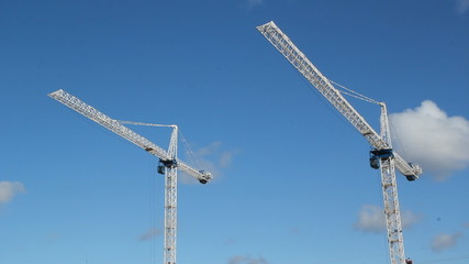 White tower cranes against blue sky. Realtime shot.