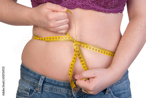 Woman measuring her belly fat