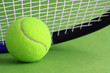 Tennis racket and ball on a green background.