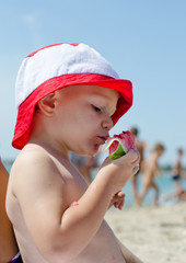 Little boy eating watermelon at the seaside