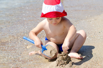 Little boy building sand castles