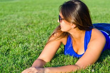 Woman relaxing lying on grass