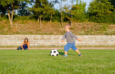 Athletic small boy playing soccer