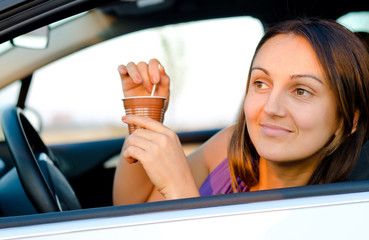 Woman enjoying coffee in her car