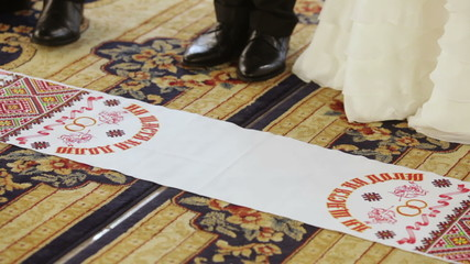 The bride and groom stand on national embroidered embroidered