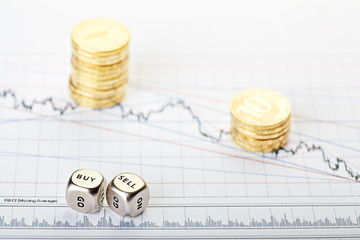 Downtrend stacks of coins and dices cubes with the words SELL BU