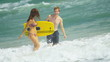 Caucasian Couple Splashing Ocean Carrying Body Boards