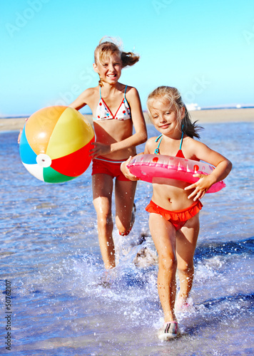 Children holding hands running on  beach.