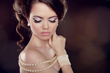 Fashion woman with a pearl necklace on the bared shoulders