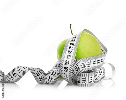 Measuring tape wrapped around a green apple