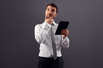 pensive man holding tablet pc