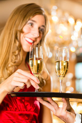 Waiter serves champagne glasses on tray in restaurant