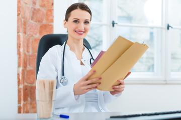 Ärztin in Praxis schreibt in Krankenakte