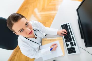 Ärztin in Praxis schreibt in eine Krankenakte