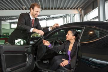 Verkäufer übergibt Schlüssel an Kundin im Autohaus