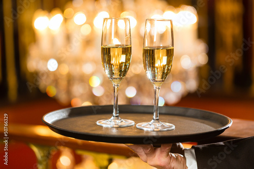Waiter served champagne glasses on tray in restaurant