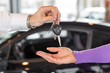 Car salesman handing over car keys in dealership