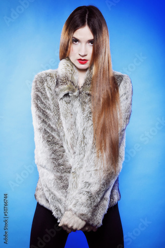 portrait of young woman in fur blue background