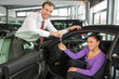Salesman in car dealership sells automobile to customer