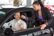 Saleswoman selling a car to happy customer