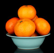 Tasty mandarines in color bowl isolated on black