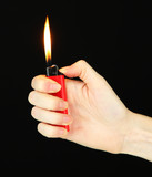Burning lighter in female hand, isolated on black