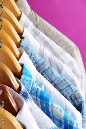 Men's shirts on hangers on purple background