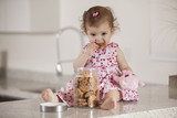 Cute little girl eating cookies from a jar