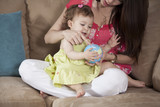 Young mother and baby girl playing with a ball