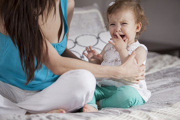 Pretty baby girl crying while her mom tries to calm her
