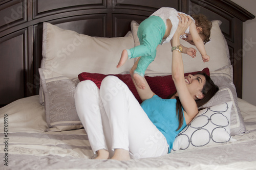 Young mother and her baby girl having fun in the bedroom