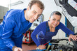 Two mechatronic technicians in a garage
