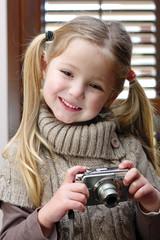 Bambina che impara ad usare una macchina fotografica