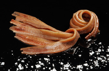 fillets of anchovies in olive oil on black background