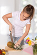 Young woman slicing pineapple