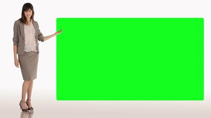 Businesswoman presenting a green screen