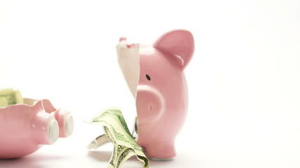 Piggy bank splitting in two with cash inside